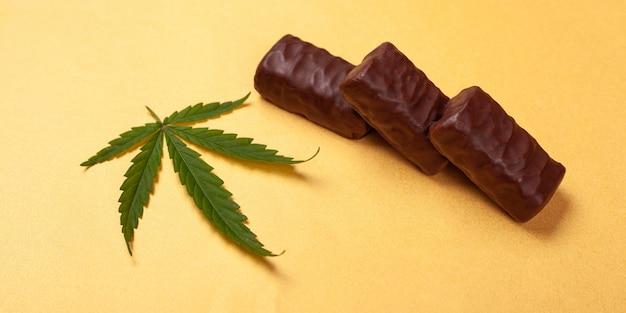 Bonbons au cannabis. bonbons au chocolat avec une feuille de marijuana sur fond jaune.
