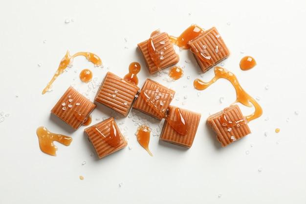 Bonbons au caramel salé et sauce sur espace blanc, espace pour le texte