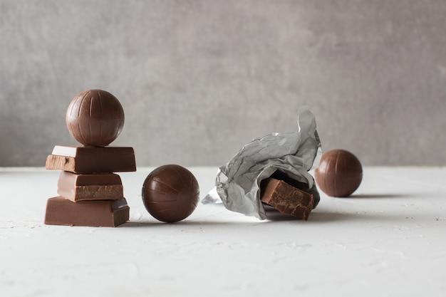 Bonbons au chocolat et des barres mordues sur la table blanche. une place pour le texte.