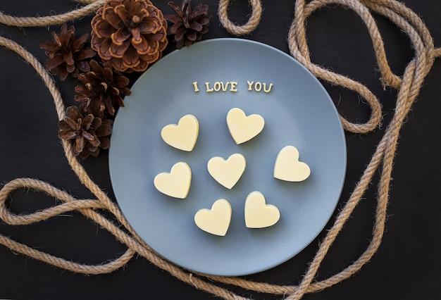 Bonbons au chocolat blanc dans un coeur, j'aime écrire sur une assiette bleue avec des cônes