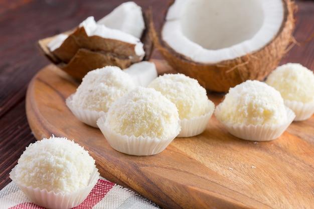 Bonbons au chocolat blanc avec garniture de noix de coco sur table en bois