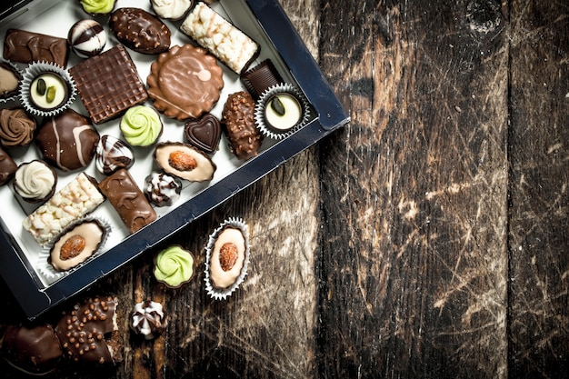 Bonbons au chocolat dans une boîte. sur un fond en bois.