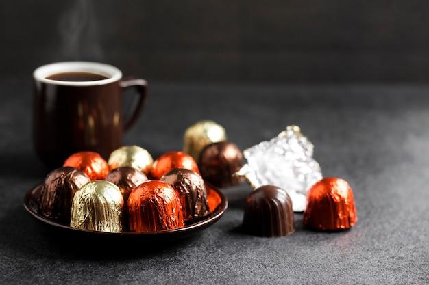 Bonbons au chocolat enveloppés dans une feuille multicolore sur une assiette et deux tasses de café chaud sur fond noir avec copie espace