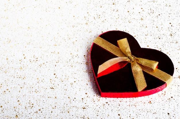 Bonbons au chocolat faits à la main dans une boîte en forme de cœur rouge avec noeud en or.