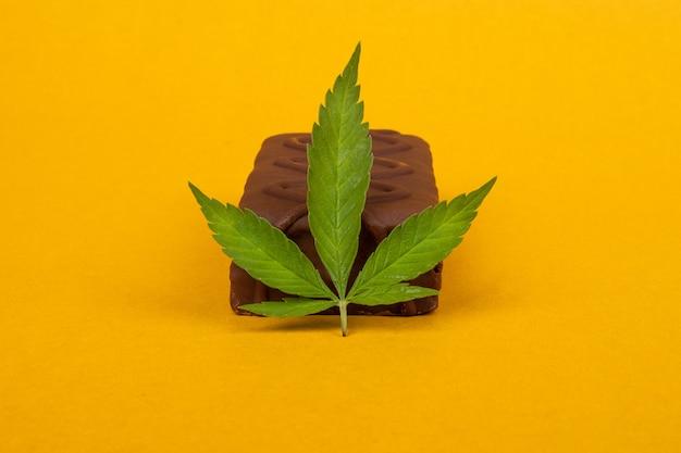 Bonbons au chocolat et une feuille de marijuana sur fond de beauté jaune. bonbons sucrés avec l'ajout d'huile de haschich.
