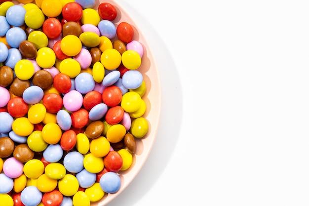 Bonbons au chocolat multicolores en plaque sur fond blanc. vue de dessus. copier l'espace