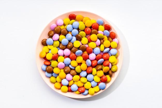 Bonbons au chocolat multicolores en plaque sur fond blanc. vue de dessus