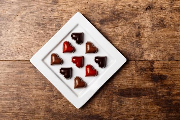 Bonbons au chocolat sur une plaque blanche sur bois