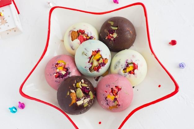 Bonbons au chocolat rose, blanc, brun et sélénium faits à la main avec une garniture aux noix sur une assiette en forme d'étoile.