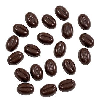 Bonbons au chocolat sous forme de grains de café isolés sur une surface blanche.