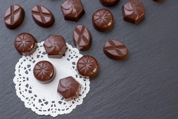 Bonbons au chocolat sur une surface noire, poudre de cacao. photo sombre, humeur.
