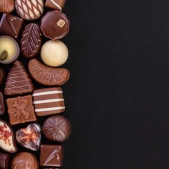 Bonbons au chocolat sur tableau noir, diverses pralines et truffes avec un espace vide