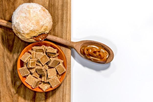 Bonbons au dulce de leche avec cuillère en bois pleine de dulce de leche et pain à la crème, connu sous le nom de boule de berlin, beignet sans trou ou boulangerie