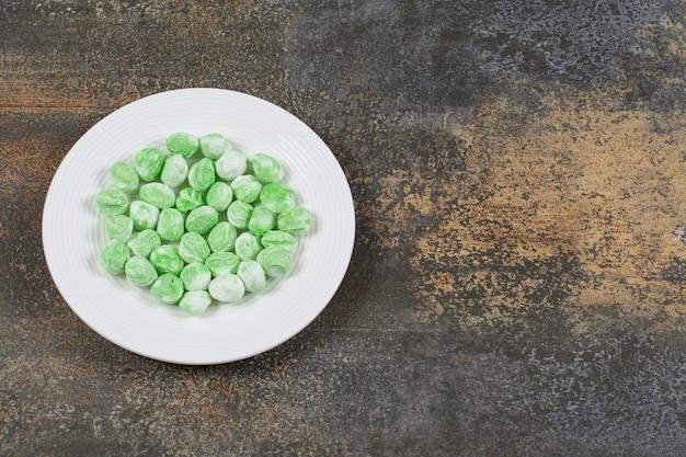 Bonbons au menthol vert sur plaque blanche.