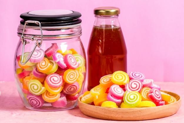 Bonbons au miel en pot sur table sur fond rose