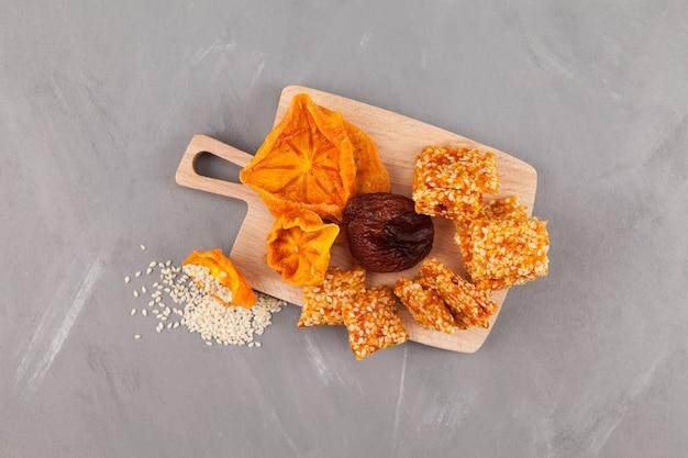 Bonbons à base de kaki séché et d'abricot avec addition de graines de sésame blanches.