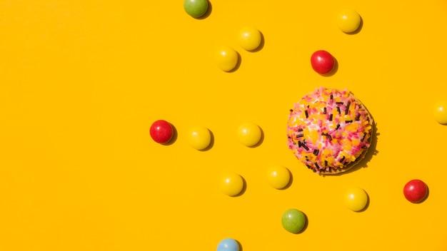 Bonbons avec beignet saupoudré sur fond jaune