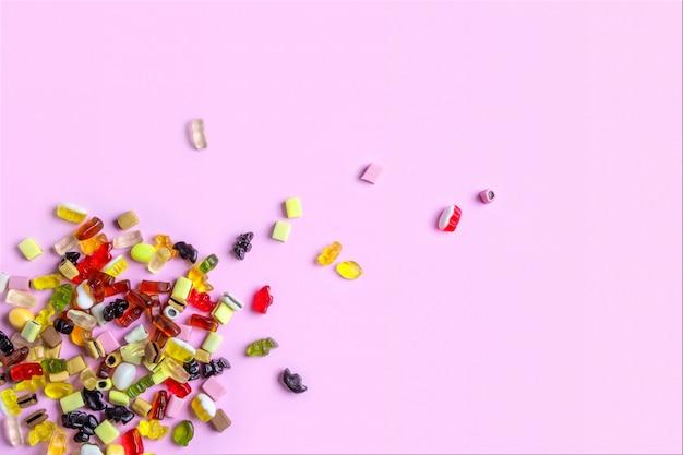 Bonbons de bonbons colorés sur une surface rose