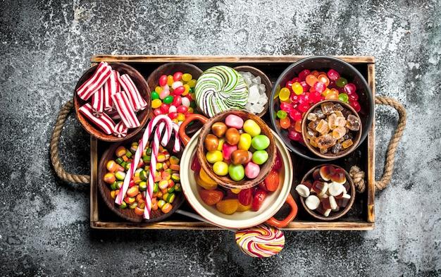 Bonbons bonbons, fruits confits à la guimauve et gelée sur un plateau en bois