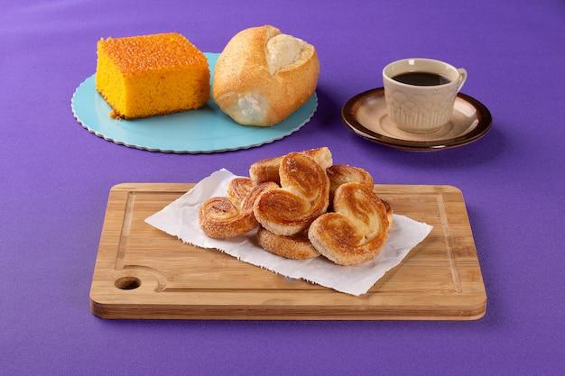 Bonbons de boulangerie sur une planche en bois avec un gâteau aux carottes et du pain français en arrière-plan à côté d'une tasse o