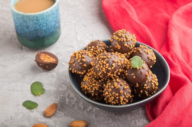 Bonbons boule chocolat caramel aux amandes et une tasse de café sur une surface de béton gris et textile rouge