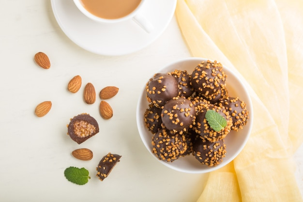 Bonbons boule chocolat caramel aux amandes et une tasse de café sur une surface en bois blanc et textile jaune