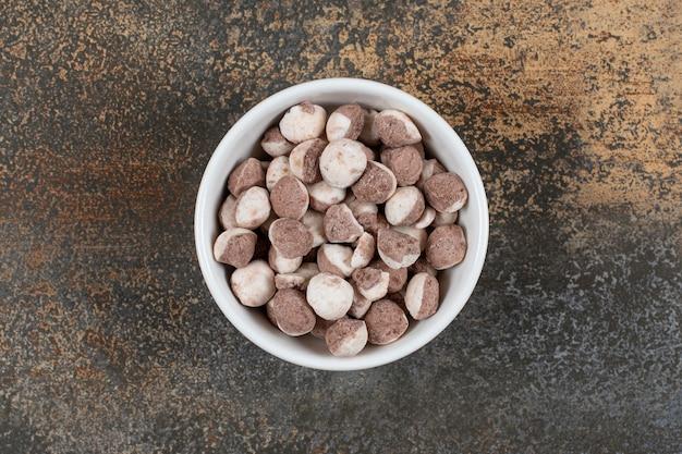 Bonbons bruns savoureux dans un bol blanc.