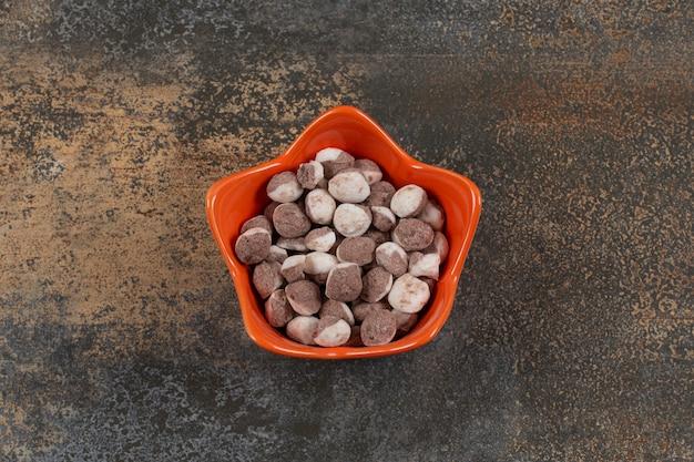 Bonbons bruns savoureux dans un bol orange.