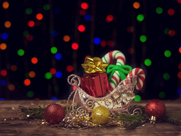 Bonbons et cadeaux de noël dans un panier décoratif sur une table en bois