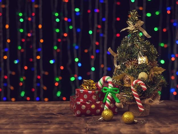 Bonbons et cadeaux de noël sous un sapin décoré.