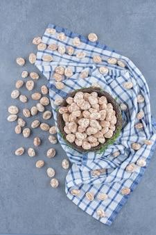Bonbons à la cannelle dans le bol, sur la serviette sur le fond de marbre.