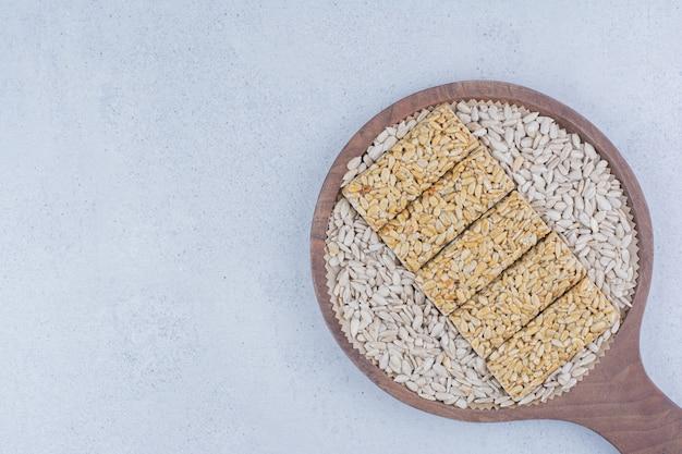 Bonbons cassants aux graines de tournesol sur une planche à découper.