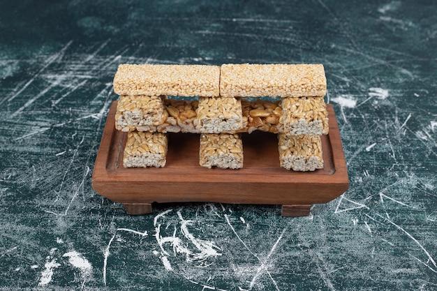 Bonbons cassants avec graines et noix sur planche de bois.