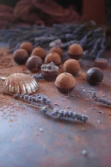 Bonbons de chocolat ronds à la lavande sur fond sombre. confiserie pour les mains