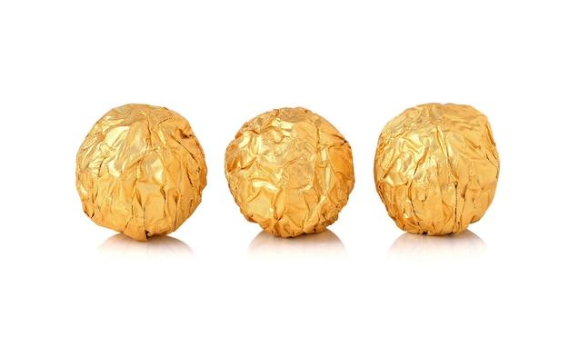 Bonbons de chocolat sucrés enveloppés dans une feuille d'or isolé sur fond blanc