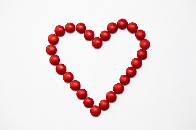 Bonbons colorés au chocolat bouton m & m en forme d'amour sur fond blanc.