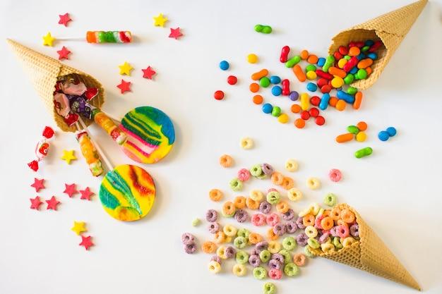 Bonbons colorés avec cornet de crème glacée à la gaufre sur fond blanc