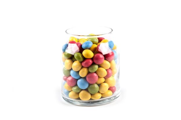 Bonbons colorés dans un bocal en verre isolé sur blanc