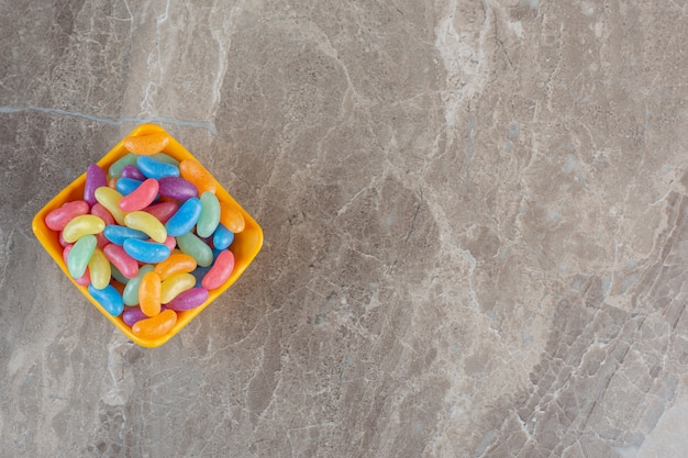 Bonbons colorés dans un bol orange sur fond gris. vue de dessus.