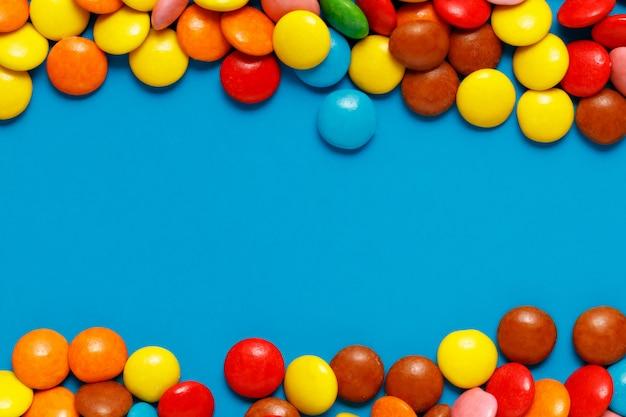 Bonbons colorés doux bouchent sur fond bleu avec copie espace pour le texte