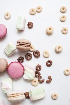 Bonbons colorés sur fond blanc macarons, zéphyrs et flocons de maïs dispersés