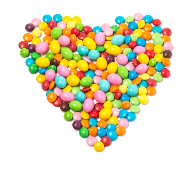 Bonbons colorés en forme de coeur sur fond blanc