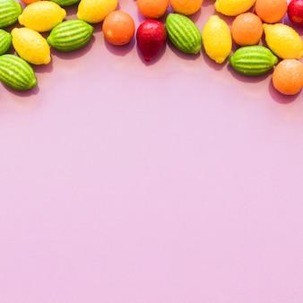 Bonbons colorés de forme de fruit formant le fond supérieur au-dessus de la toile de fond rose
