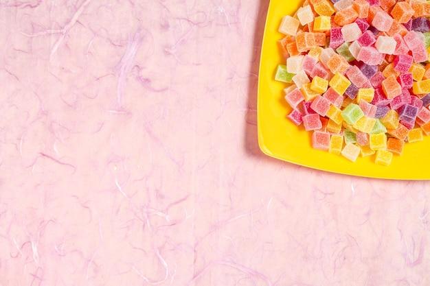 Bonbons colorés et gelée dans un plat de couleur sur fond rose