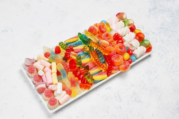 Bonbons colorés, gelée, guimauve sur une surface claire. vue de dessus avec espace copie