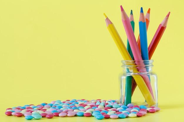 Bonbons colorés et pot sur un mur jaune