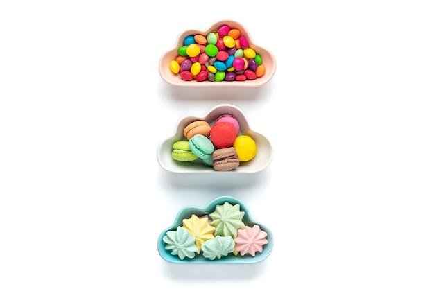 Bonbons colorés - sucettes, meringues, macaron dans un bol en forme de nuage isolé sur blanc