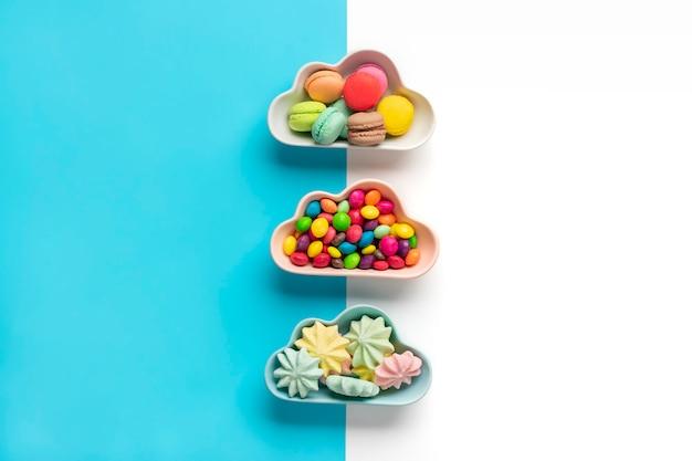Bonbons colorés - sucettes, meringues, macaron dans un bol en forme de nuage isolé sur bleu, blanc