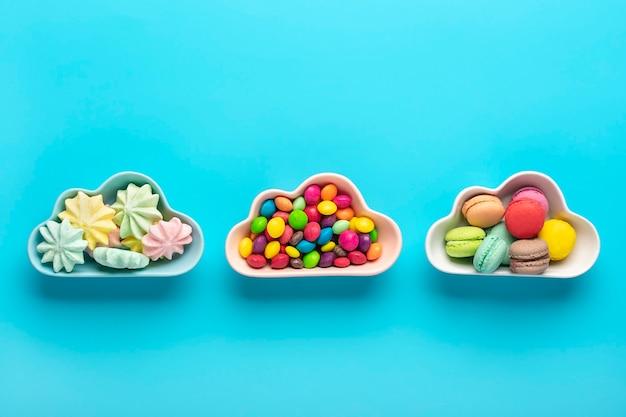 Bonbons colorés - sucettes, meringues, macaron dans un bol en forme de nuage isolé sur bleu