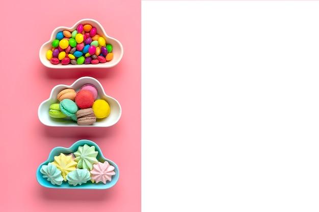 Bonbons colorés - sucettes, meringues, macaron dans un bol en forme de nuage isolé sur rose, blanc